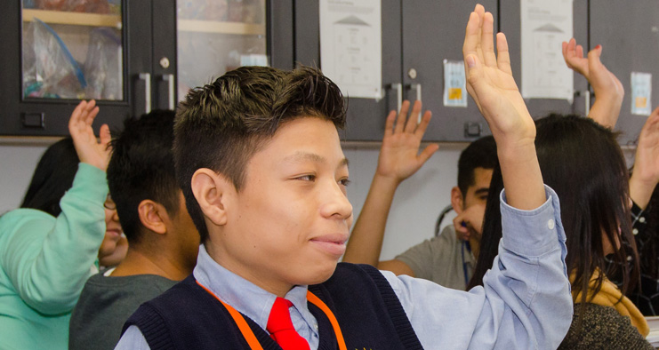 Image of Christopher Lopez raising his hand in a classroom