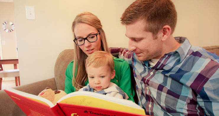 Mikaela and her husband read a book to her child